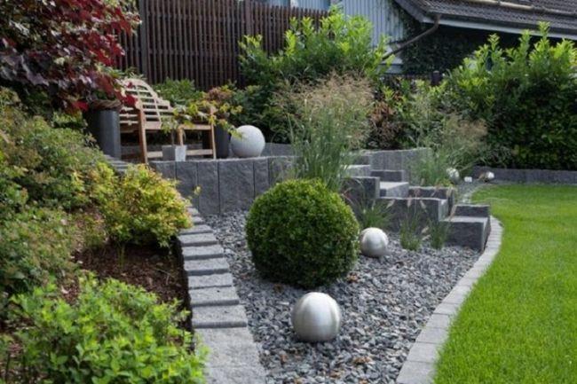 Металлические и каменные сферы на территории садового участка.